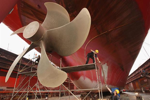 Workers remove scaffolding after maintenance work on a cargo ship's propeller in Hamburg, Germany. The shipping industry is responsible for around 3% of global CO2 emissions. Photo: Photo by Sean Gallup/Getty Images