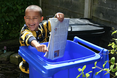 Boy putting paper in blue recyling bin (credit: Royal Borough of Windsor and Maidenhead)