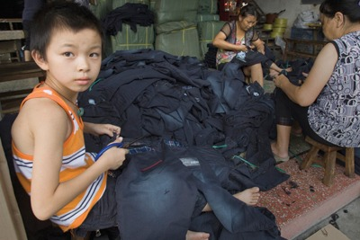 A young boy is working with his parents at a small jeans workshop in Dadun Village in Xintang, Zengcheng (credit: Lu Guang / Greenpeace)