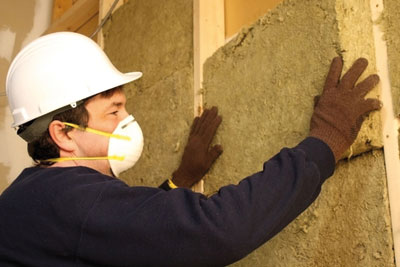 Insulation being installed in wall (credit: dreamstime.com)