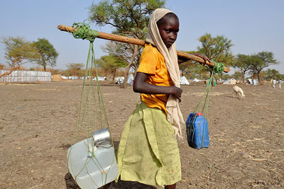 Young girl carrying water in South Sudan (photograph: Alun McDonald/Oxfam)