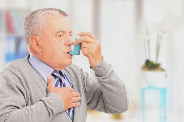 An asthmatic man using an inhaler