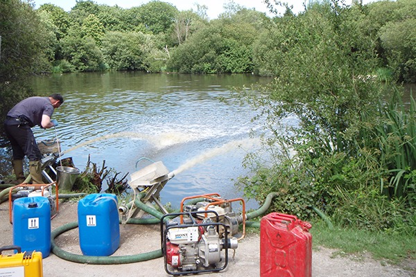 Environment Agency staff working to restore dissolved oxygen levels at Par Pond where hundreds of small coarse fish died. Photograph: Environment Agency