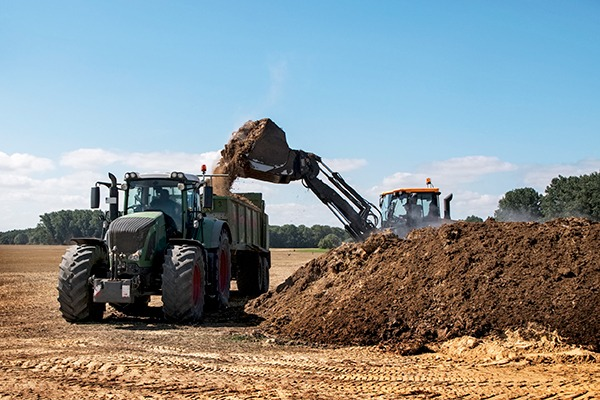 Excavator filling manure in the trailer of a tractor to fertilise the field. Photograph: Fermate/123RF