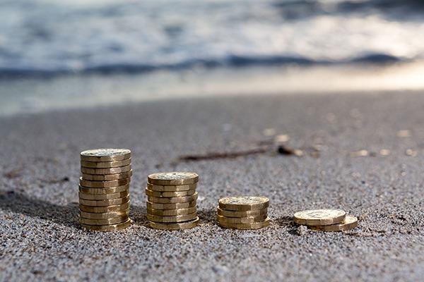 Row of pound coins piled on beach.