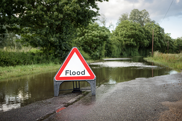 Flood warning sign on flooded road