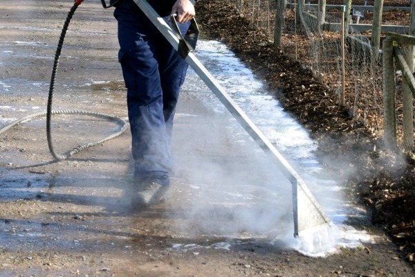 Worker using Foamstream to kill weeds