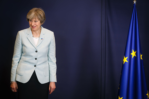 Theresa May standing next to EU flag