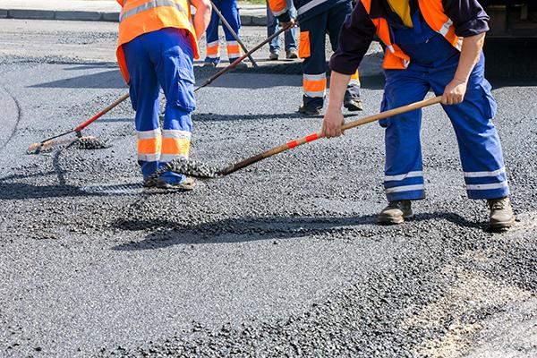 Workers repairing road surface