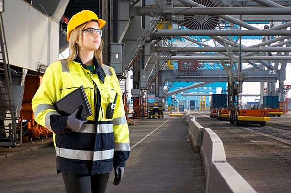 Woman in hi vis jacket with hard hat holding clipboard