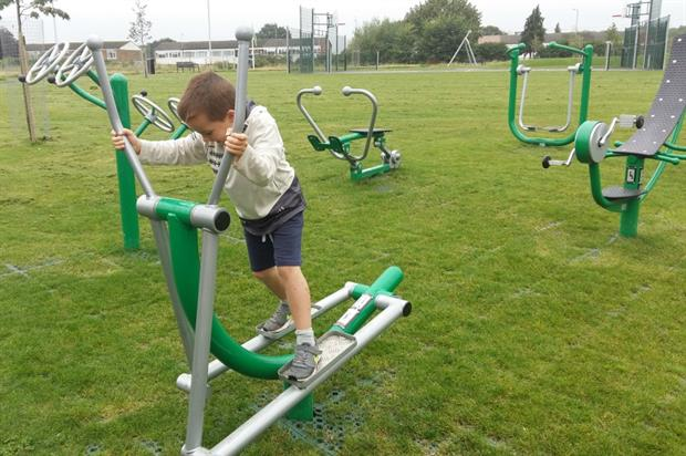 A boy tries out the green gym in Centenary Park. Image: Rugby Borough Council