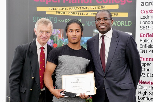 Capel Manor College student Matthew Ogunmokun receives Silky Fox Handsaw Award from RFS regional chairman Paul Akers and former minister David Lammy MP