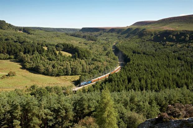 A train travels through the Levisham Estate. Image copyright Chris Ceaser
