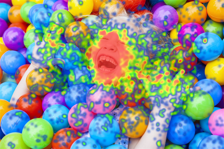 An image of a child in a ballpit with a heatmap showing where most people's eyes were drawn