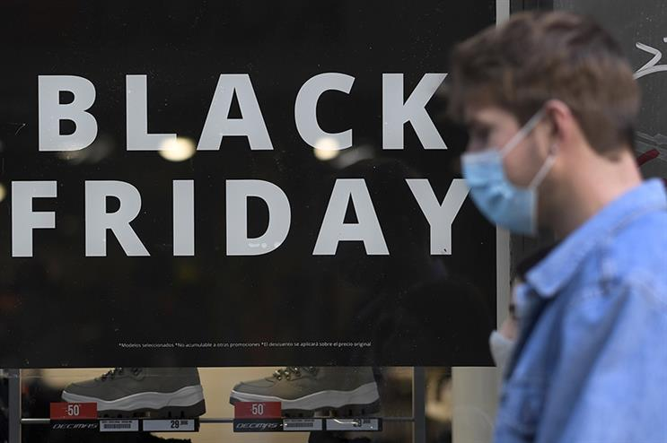 A sign announces a price markdown for Black Friday on the display window of a shop in Madrid. ( GABRIEL BOUYS/AFP via Getty Images)