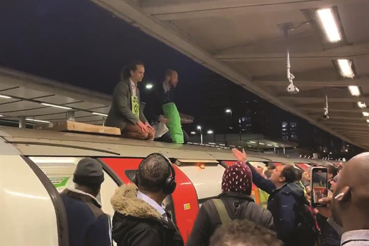 Extinction Rebellion protestors hold up a train at Canning Town tube station