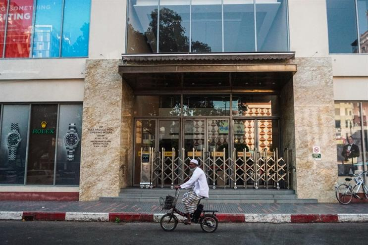 A man cycles past an empty shopping mall in Yangon (Getty Images)