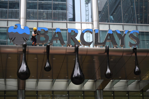 Greenpeace activists created a mock tar sands oil spill at Barclays headquarters on Thursday morning