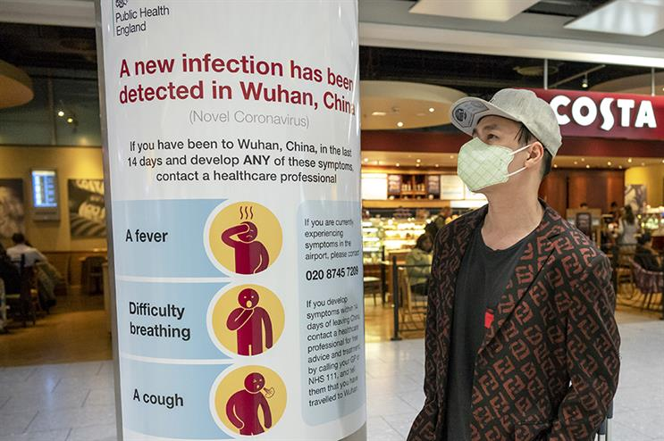 A man looks at Public Health England's infection control poster at Heathrow (Alex Lentati/LNP/Shutterstock)
