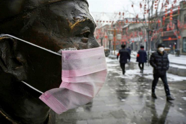 A protective mask is seen on a statue outside a restaurant as people walk by in an empty and shuttered commercial street in in Beijing