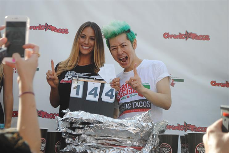 Takeru Kobayashi celebrates his 2015 win, consuming 140 tacos in 10 minutes. The initial tally was 144 but was decreased due to leftover table scraps.