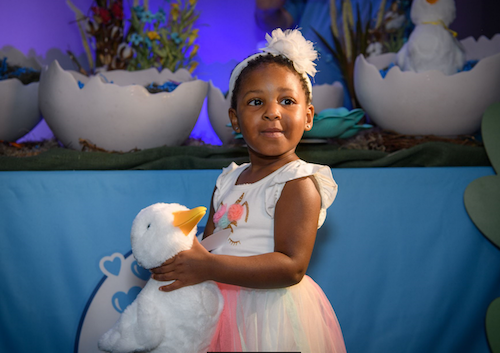little girl holding a My Special Aflac duck toy