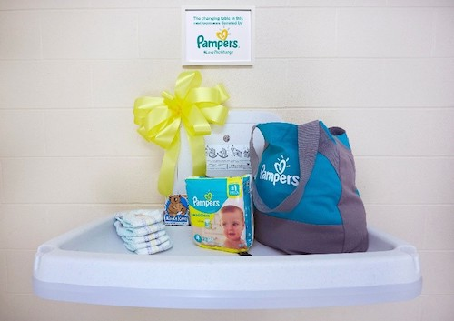 a changing table with Pampers diapers and a diaper bag on it