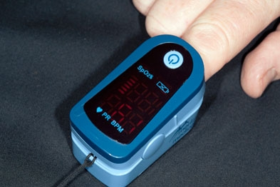 Adult pulse oximeter (blood oxygen meter) fitted to the finger of an adult to measure pulse rate and oxygen concentration of the blood. (SPL)