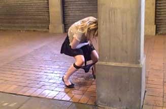 Woman peeing in the street
