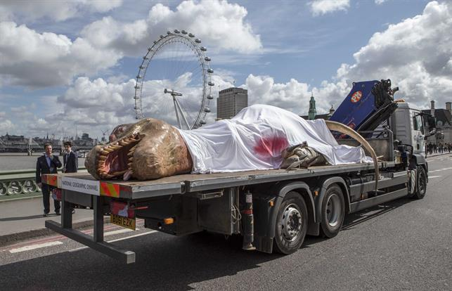 The dinosaur was laid out and strapped to a flatbed truck, partially covered by blood-soaked sheets