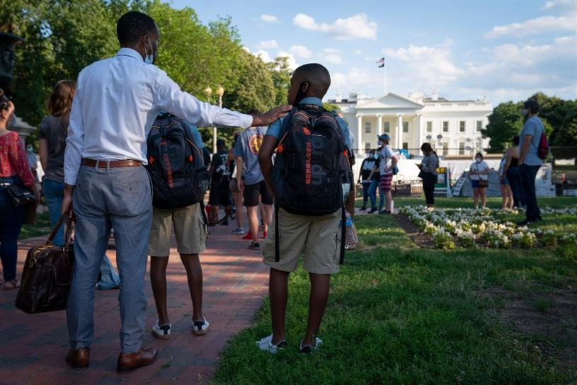 WASHINGTON, DC - JUNE 12: A father and son participate in a peaceful Black Lives Matter protest near the White House on June 12, 2020 in Washington, DC. Protests continue in cities throughout the country over the death of George Floyd, who died while