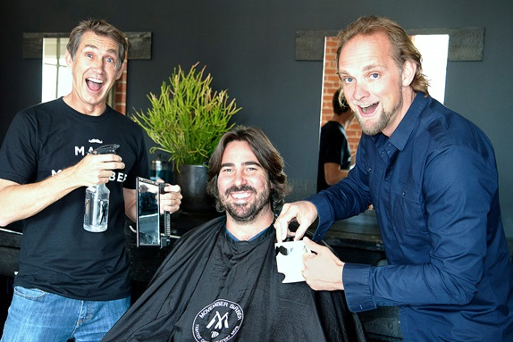 Movember Foundation SVP Mark Fewell (left) and Sid Lee USA CEO Will Travis (right) clean up Sid Lee LA Managing Partner Nicolas Van Erum (seated) for Movember