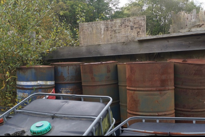The barrels at Stoney Castle are suspected of containing PCBs. At least one is labelled as containing insulating oil. Photograph:  Surrey's largest illegal waste dump