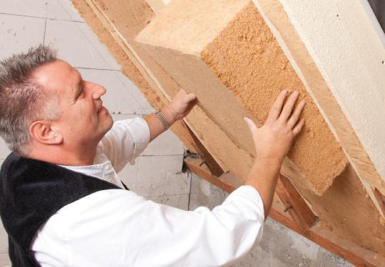 A worker installs Kronopoly made insulation