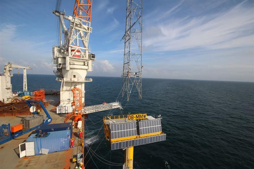 The lattice tower is lowered onto the platform of Dogger Bank met mast west