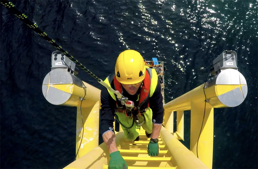 An engineer accessing an offshore wind turbine to carry out O&M activities