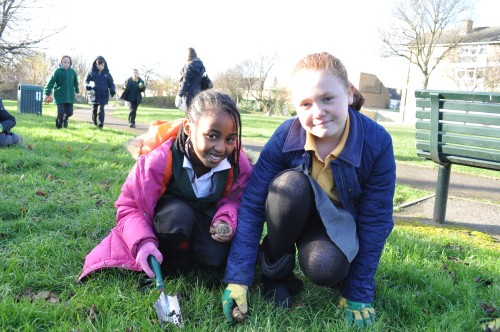 Two young volunteers planting bulbs at King George's Playing Fields