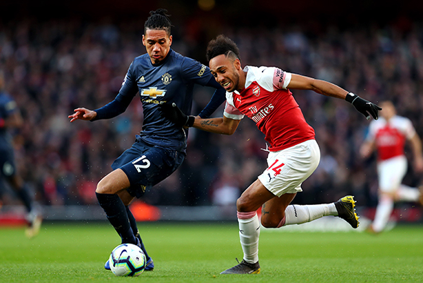 Manchester United defender Chris Smalling (l) challenges Arsenal striker Pierre-Emerick Aubameyang. (©Catherine Ivill/Getty Images)