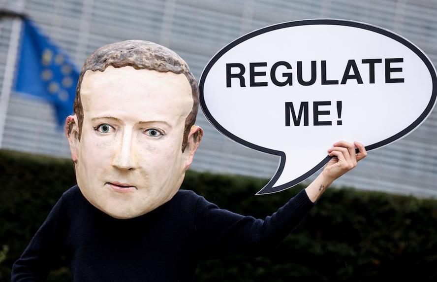 A mask-wearing activist depicting Facebook CEO Mark Zuckerberg outside the European Commission in Brussels last December. (Credit: Getty Images)
