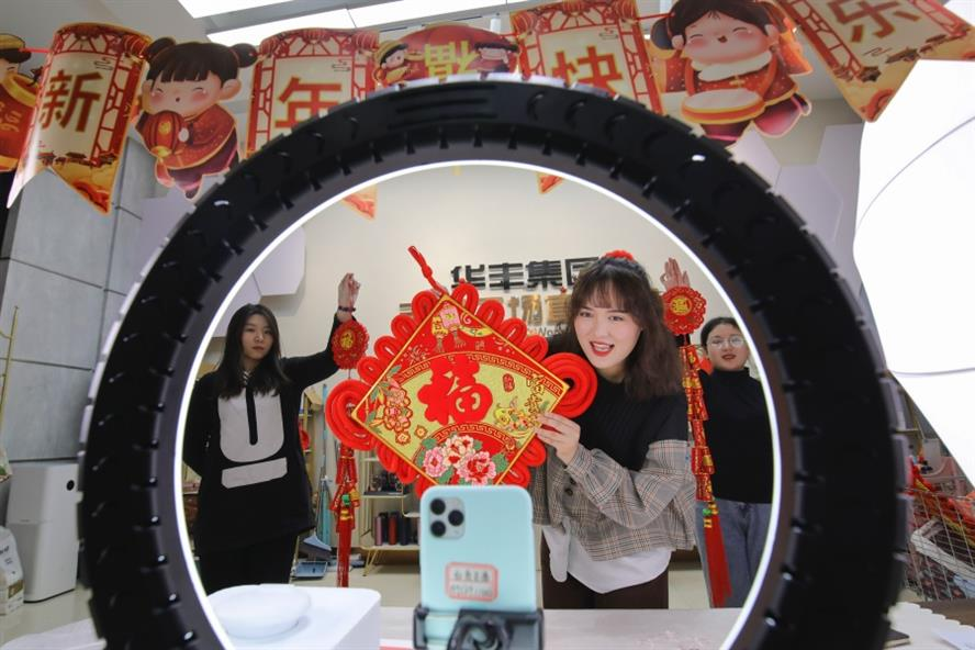 A livestreamer sells CNY decorations on a smartphone in Linyi, Shandong Province of China. (Getty Images)