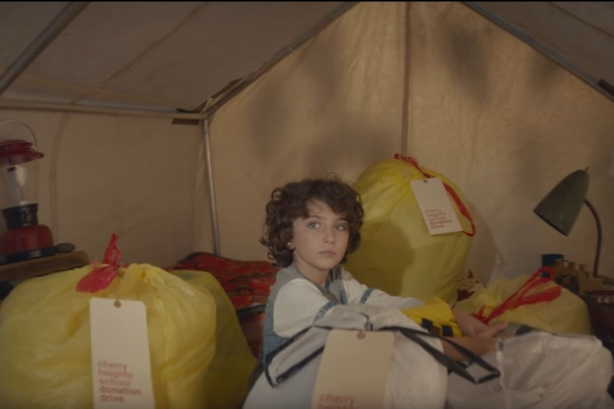 The anthem video tells the story of a boy giving away his personal possessions to charity. (Image via YouTube).
