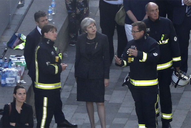 Theresa May meets firefighters as she visits Grenfell Tower (Credit: TOLGA AKMEN/AFP/Getty Images)