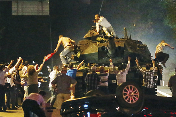 Unrest: A tank moves into position as people attempt to stop it, in Ankara, Turkey on 16 July (AP Photo)