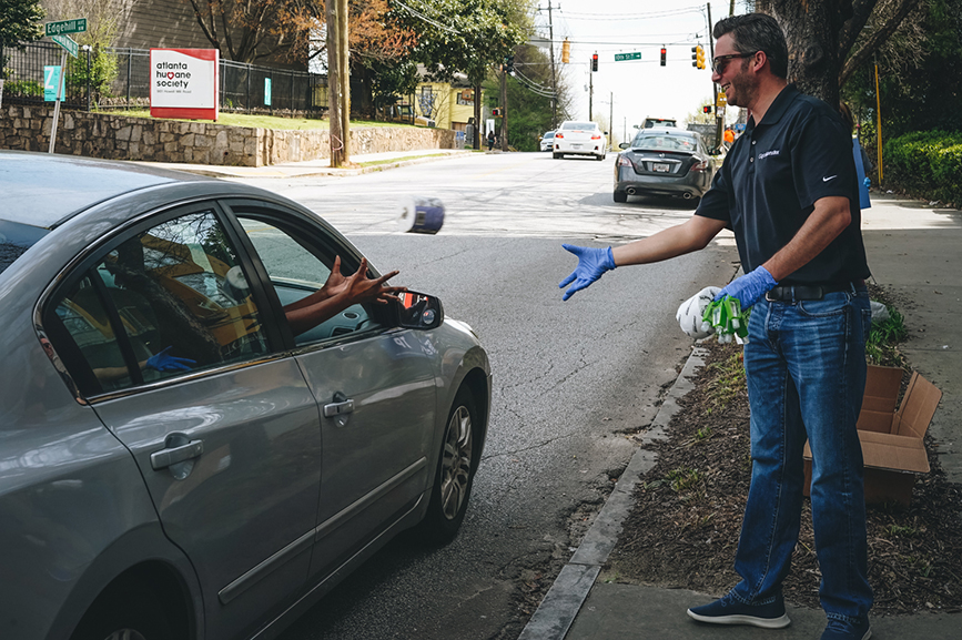 A.J. Whitehurst, director of field operations at GigaMonster tosses a roll of toilet paper into a waiting car. (Photo credit: Rose Rosenhauer, Trevelino/Keller)
