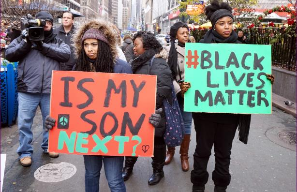 Protestors carrying placards at a Black Lives Matter demonstration in New York City (Image via Wikipedia Commons)