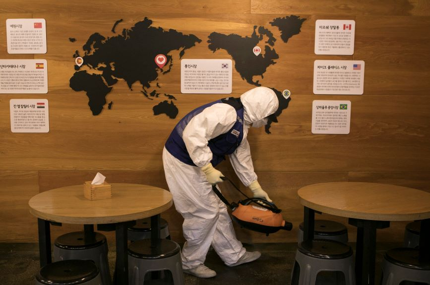 A disinfection worker in protective gear sterilizes a restaurant in Seoul, South Korea. (Photo credit: Getty Images)