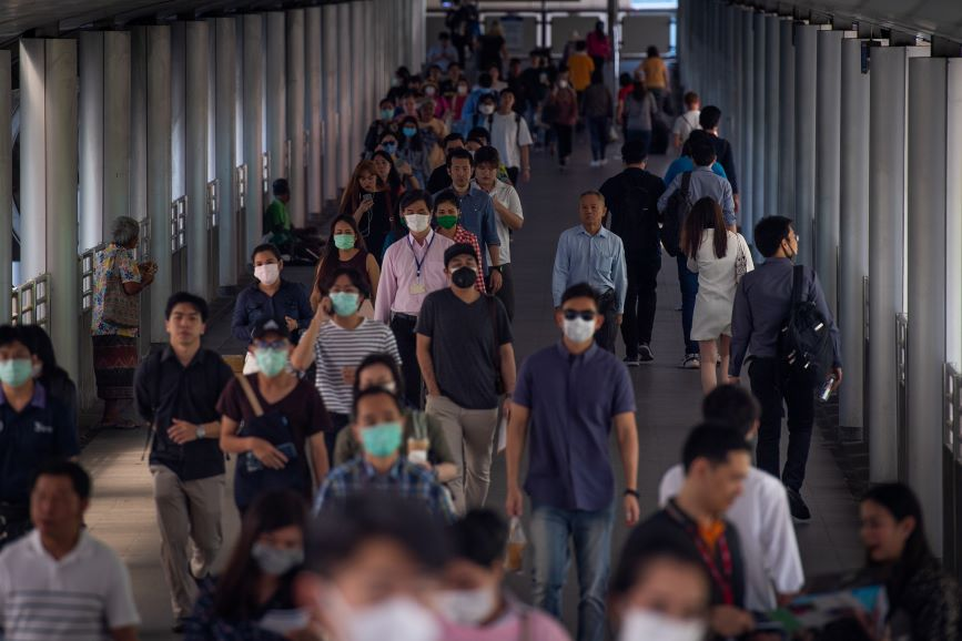 Pedestrians wear protective masks as a measure against coronavirus in Bangkok, where companies like Omnicom have postponed business travel. (Photo credit: Getty Images)