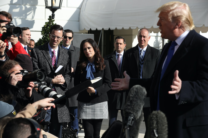 Grisham, center, watches President Trump brief the press last November. (Photo credit: Getty Images)