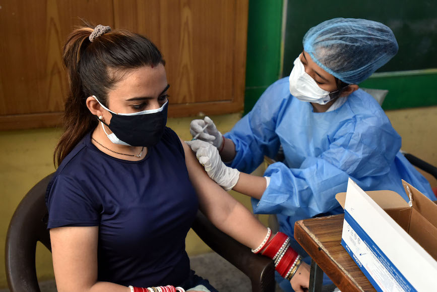 A medical worker dispenses vaccines in New Delhi. (Credit: Getty Images).