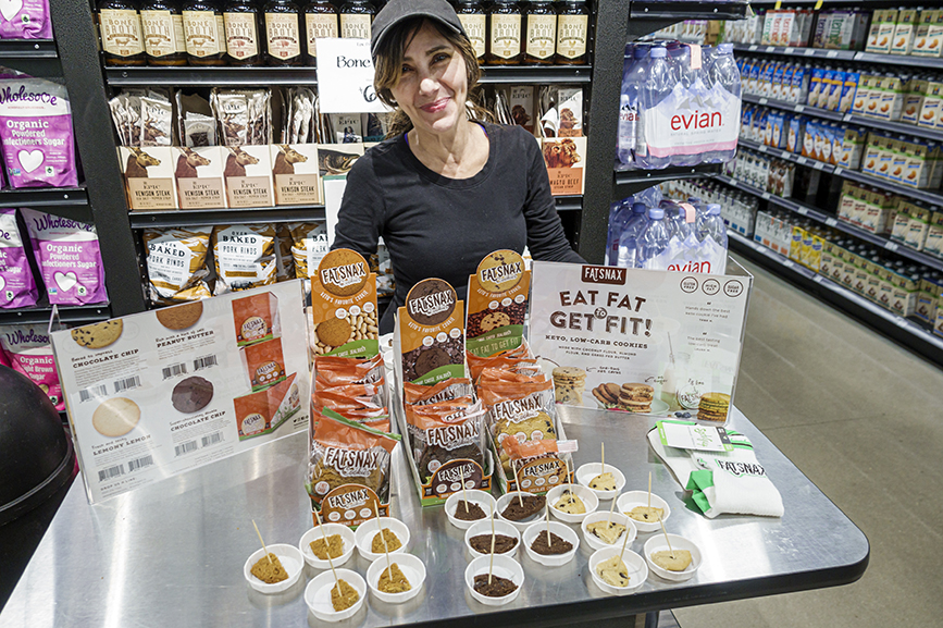 In a Whole Foods Market, a woman distributes free food samples. (Photo by: Jeff Greenberg via Getty Images)